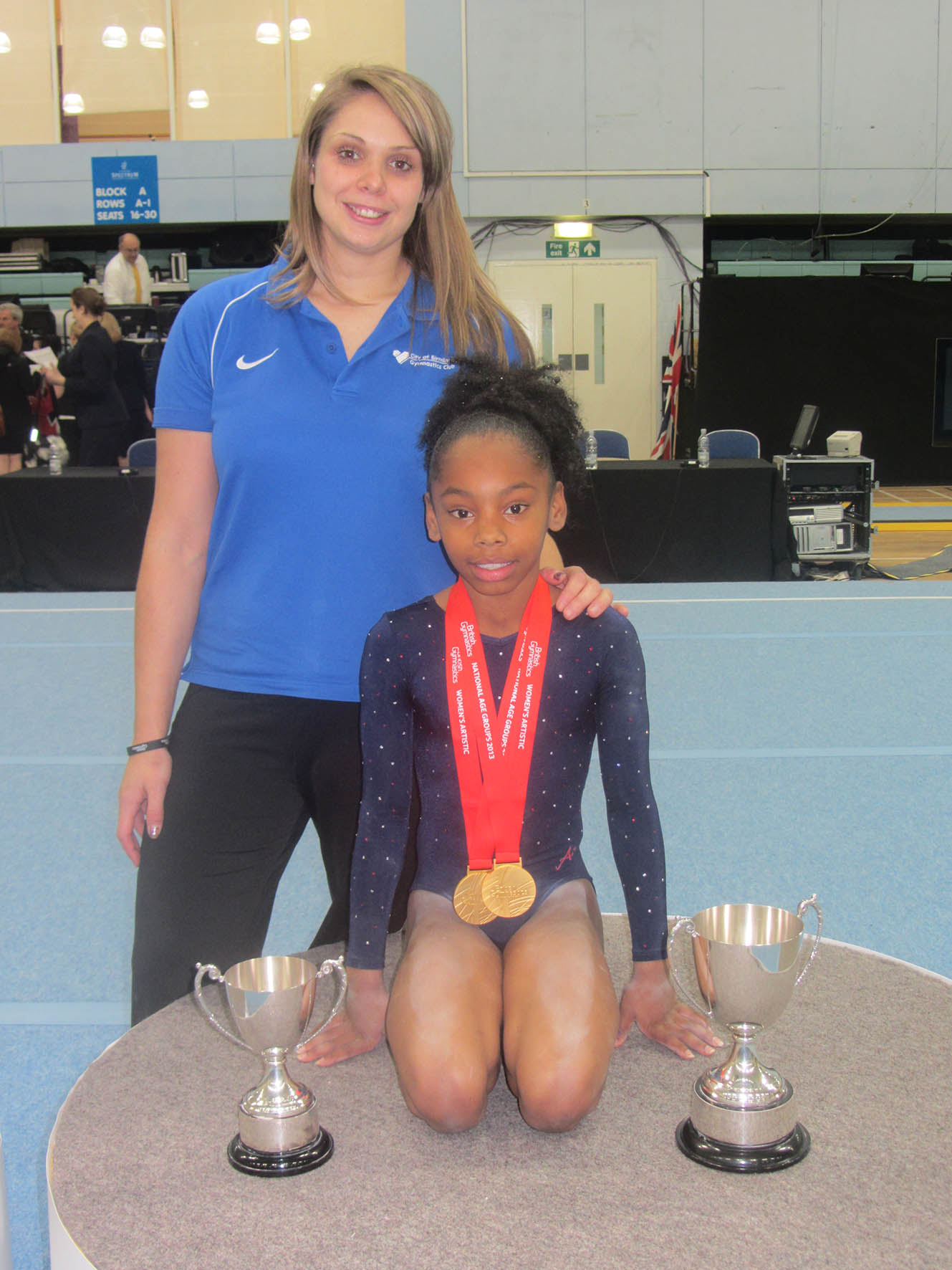 Triumphant Coach, Jody Kime, & gymnast Taeja with their British Championship trophies