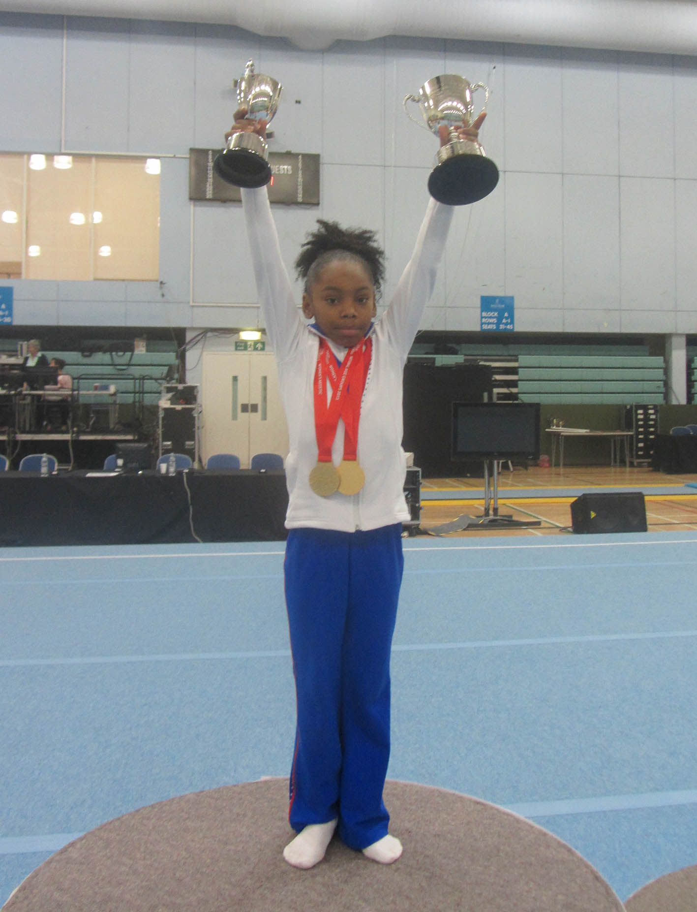 Taeja holding her Voluntary Level 2 championship trophies