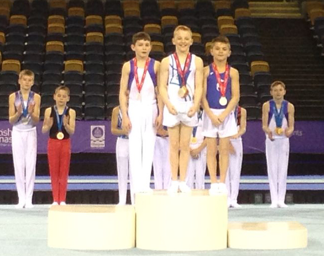 Thomas, left, takes U.12 Individual apparatus bronze medal on Pbars
